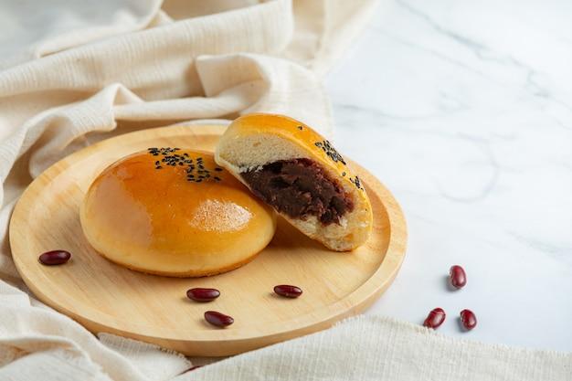 Pãezinhos de pasta de feijão vermelho assados em placa de madeira