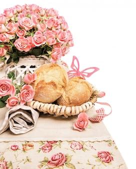 Pãezinhos de pequeno-almoço fresco com rosas em branco, espaço de texto