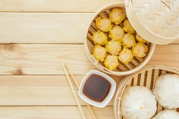 Pãezinhos de porco cozido no vapor (dim sum chinês) em cesta de bambu em fundo de mesa de madeira