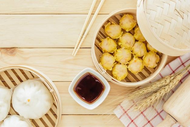 Pãezinhos de porco cozido no vapor (dim sum chinês) em cesta de bambu na mesa de madeira