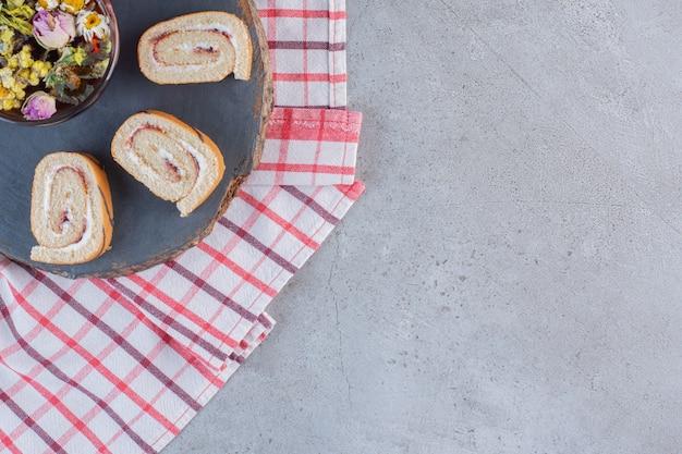 Pãezinhos doces com sabor de baunilha e xícara de chá em um pedaço de madeira.