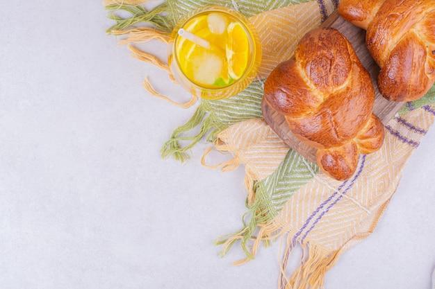 Pãezinhos doces em uma travessa de madeira com um copo de limonada.