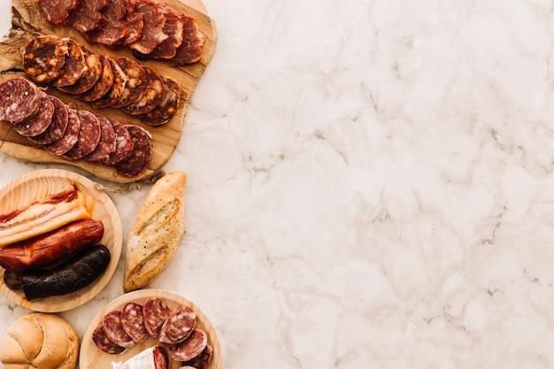 Pãezinhos e salsichas na mesa de mármore