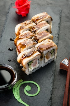 Pãezinhos e sushi em um fundo preto ardósia, cozinha japonesa