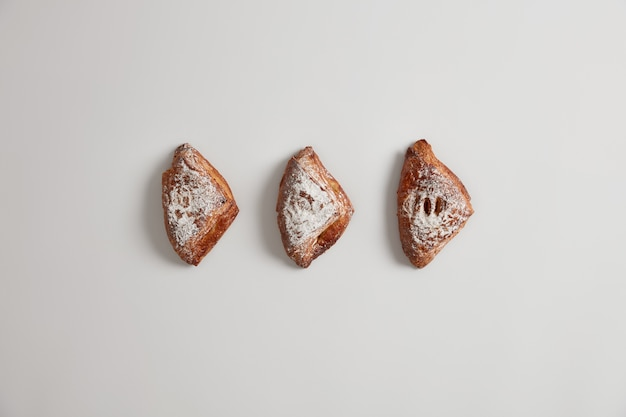 Pãezinhos folhados caseiros frescos, recheados com algo saboroso, polvilhado com açúcar, isolado no fundo branco. deliciosos pastéis doces. cozimento apetitoso fresco. conceito de junk food e nutrição