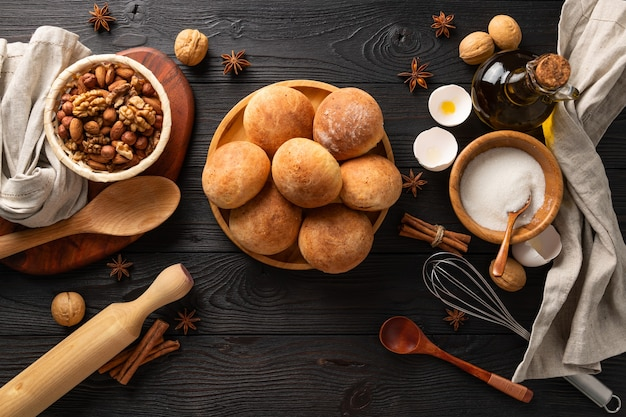 Pãezinhos frescos cozidos para o café da manhã em uma superfície de madeira entre os ingredientes, plana leigos