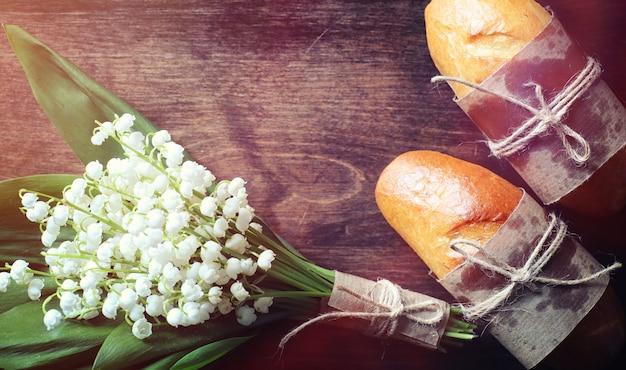 Pãezinhos frescos para o café da manhã. bun com manteiga para uma xícara de café da manhã. café da manhã no hotel pães chá de geléia e um buquê de flores.