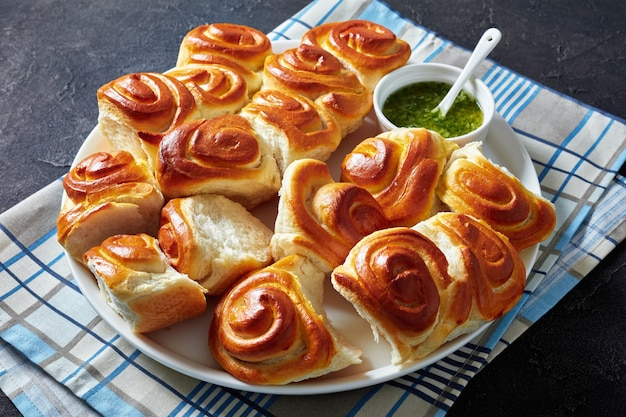 Pãezinhos quentes recém-assados, pãezinhos de fermento caseiro em uma travessa branca com molho de salsa e alho em uma tigela sobre uma mesa de concreto, vista horizontal de cima, close-up