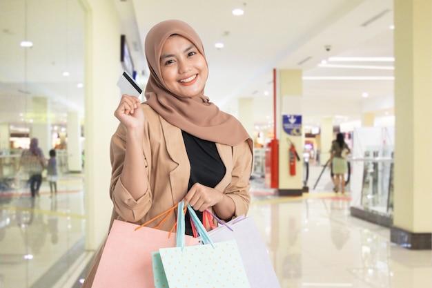Pagamento com cartão de crédito. mulher muçulmana segurando sacola de compras no shopping