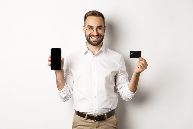 Pagamento comercial e online. homem bonito sorridente mostrando a tela do celular e o cartão de crédito em pé