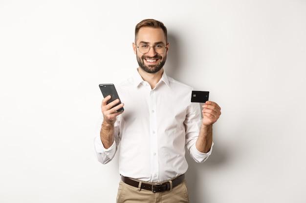 Pagamento comercial e online. sorridente empresário masculino compras com cartão de crédito e telefone celular, em pé sobre um fundo branco.
