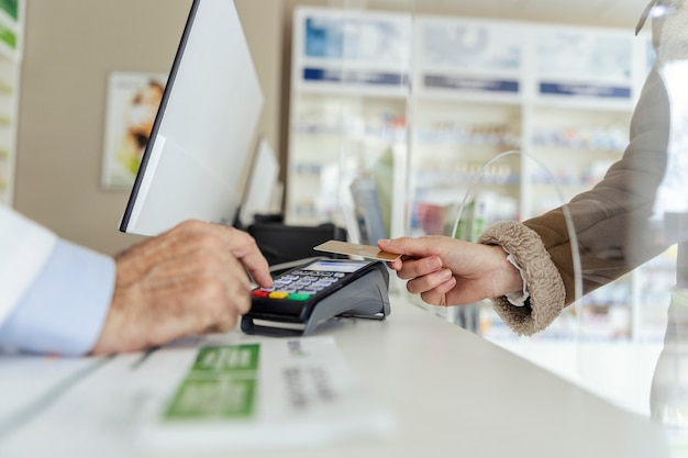 Pagamento de contas de medicamentos. close do terminal de pagamento no balcão e varredura do cartão para compra de remédios na farmácia. mãos femininas e masculinas em foco