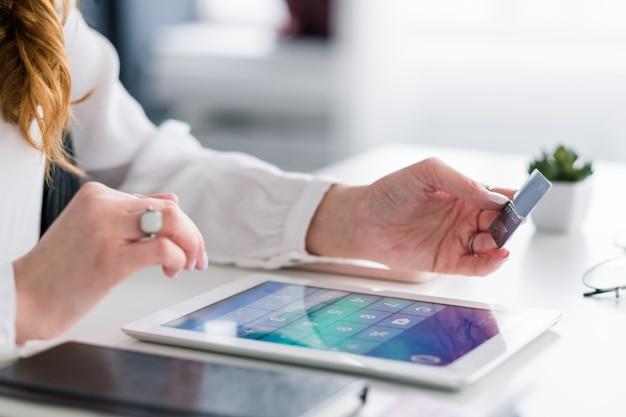 Pagamento de e-commerce. acesso a operações bancárias via internet. mulher com tablet e cartão de crédito, tornando a transação.