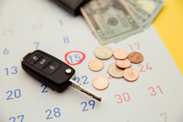 Pagamento do carro com chave do carro e abridor remoto em um calendário.