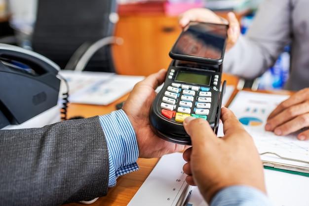 Pagamento do homem de negócio pela tecnologia de nfc com máquina do leitor de cartão de crédito e app do smartphone.