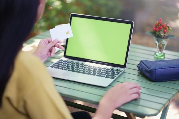Pagamento em linha, mulher que guarda o cartão de crédito e que usa o laptop para a compra em linha.