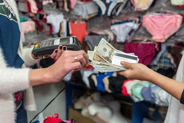 Pagamento em loja de roupas íntimas com cartão de crédito e dólares