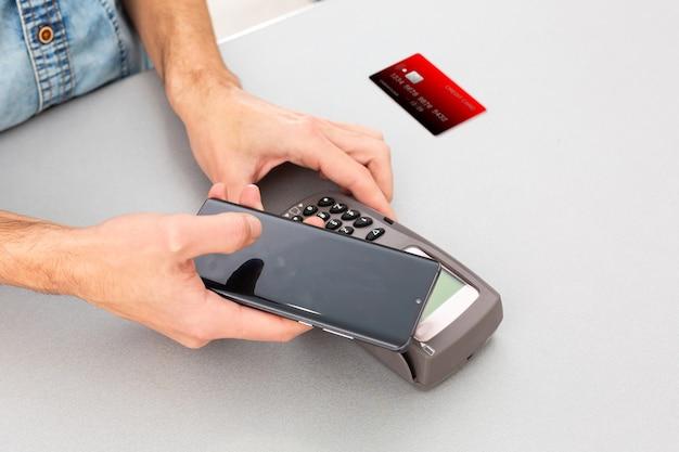Pagamento em uma transação por meio de cartão sem contato e tecnologia nfc. vista frontal. composição horizontal.