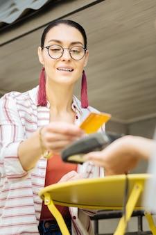 Pagamento facilitado. visitante positivo de um café local sorrindo enquanto usa um cartão de crédito e paga com a ajuda de um terminal