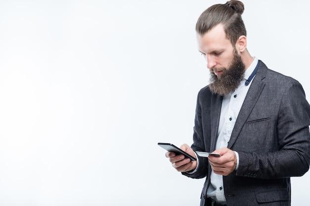 Pagamento móvel e transações nfc. finanças digitais. homem segurando o cartão de crédito e o telefone.