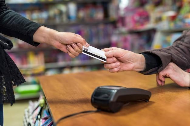 Pagamento na loja de brinquedos com dólares e cartão de crédito