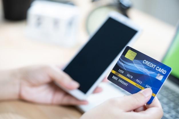 Pagamento on-line, as mãos de mulheres segurando um cartão de crédito e usando telefone inteligente
