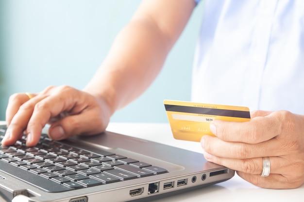 Pagamento on-line, as mãos do homem segurando um cartão de crédito e usando o laptop para compras on-line