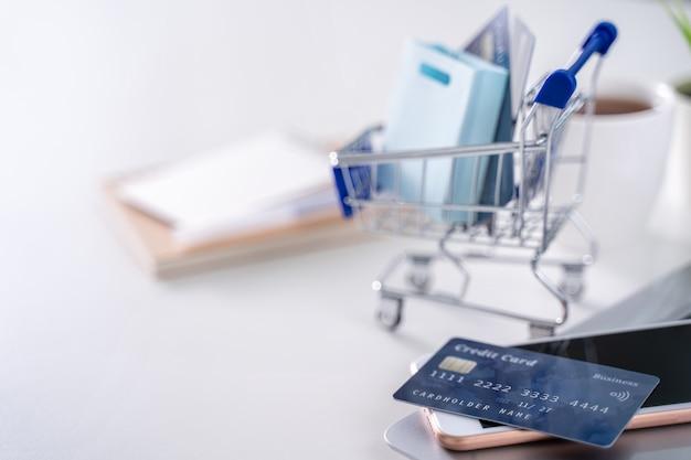 Pagamento on-line do escritório, compras em casa, pagamento eletrônico com o conceito de cartão de crédito, laptop em fundo de mesa branca com carrinho de loja, close-up.