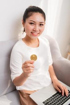 Pagamento online, mulher com as mãos segurando um bitcoin e usando o laptop do smartphone para fazer compras on-line criptomoeda
