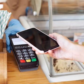 Pagamento sem contato de close-up com telefone celular