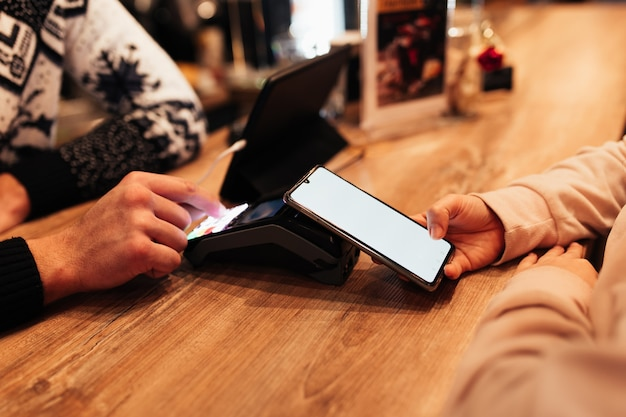 Pagamento sem dinheiro com nfc e telefone em um terminal de café. fundo desfocado.