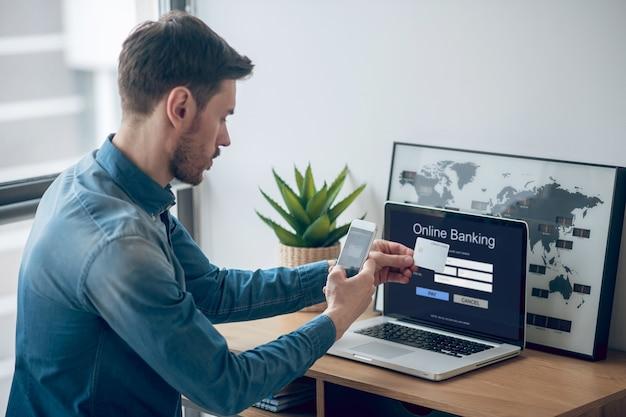 Pagamentos online. jovem com camisa jeans fazendo pagamentos periódicos online