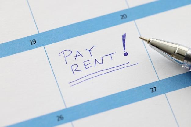 Pagar aluguel é escrito na folha do calendário com closeup de caneta esferográfica. lembretes