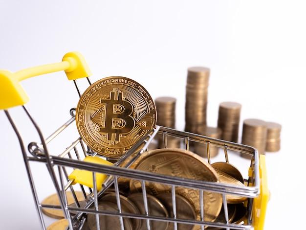 Pagar moeda criptografada: o carrinho de supermercado é preenchido com moedas de ouro de bitcoin em um fundo branco. copie o espaço