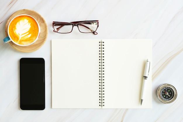 Página aberta de notebook com móvel, óculos, bússola, caneta e xícara de café sobre fundo branco de mesa