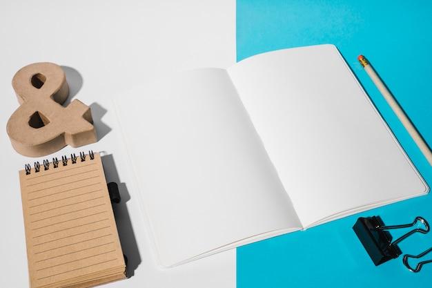 Página branca; clipe de buldogue; lápis; símbolo de e comercial e bloco de notas em espiral no duplo pano de fundo