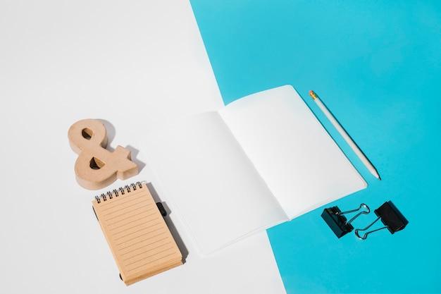 Página branca; clipes de buldogue; lápis; símbolo de e comercial e bloco de notas em espiral no duplo pano de fundo