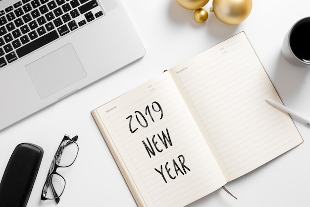 Página de caderno com texto de plano 2019 na mesa de mesa de escritório branco