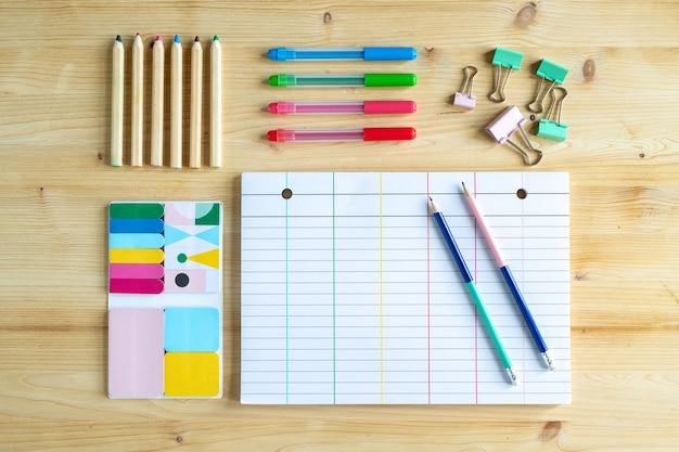 Página de caderno em branco com dois lápis e um grupo de clipes, conjuntos de giz de cera e borrachas nas proximidades
