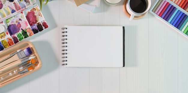 Página de caderno vazio com ferramenta de pintura de cor de água no estúdio criativo