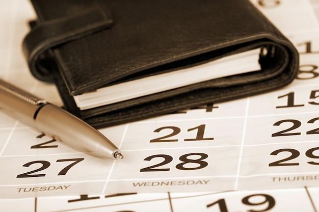 Página de calendário, caneta e planejador de bolso
