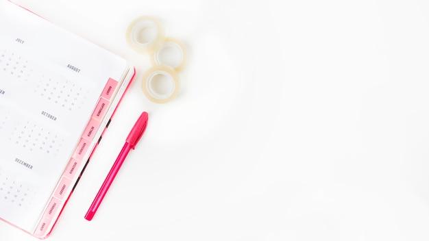 Página de calendário; caneta e violoncelo em fundo branco