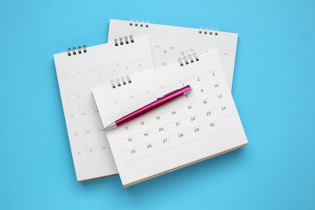 Página de calendário com caneta fechar na mesa azul, conceito de reunião de compromisso de planejamento de negócios