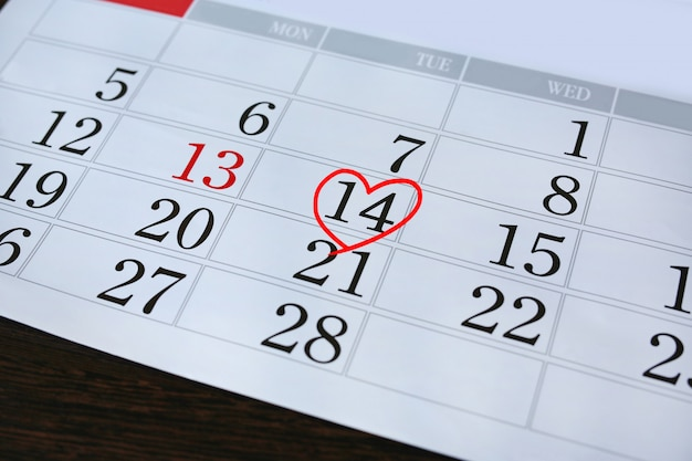 Página de calendário com uma mão vermelha escrita coração destaque em 14 de fevereiro de dia de são valentim.