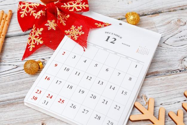 Página de calendário de dezembro com fita vermelha em fundo de madeira