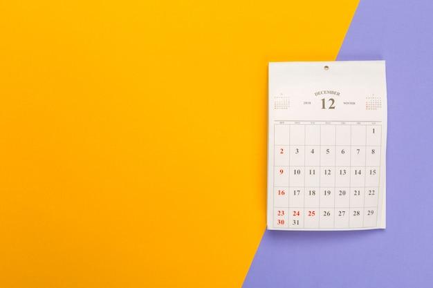 Página de calendário na superfície bicolor brilhante, vista superior