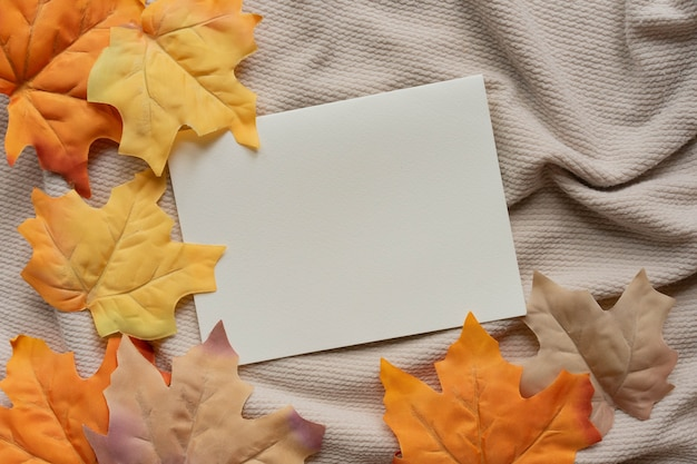 Página de papel em branco com um grupo de folhas secas de bordo de cor laranja em um fundo de tecido ondulado