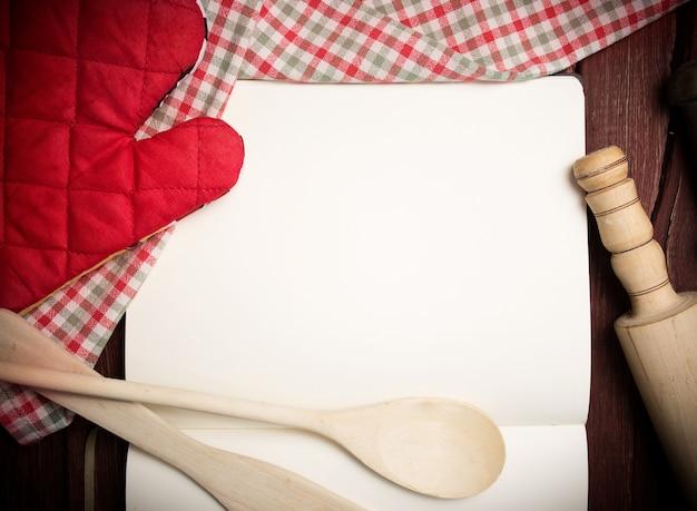 Página de receita em branco com guardanapo e utensílios de cozinha na mesa de madeira