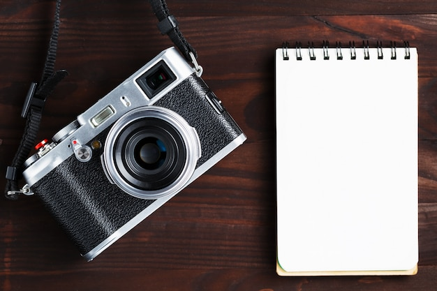 Página do bloco de notas em branco e câmera moderna em estilo clássico na mesa de madeira marrom escura