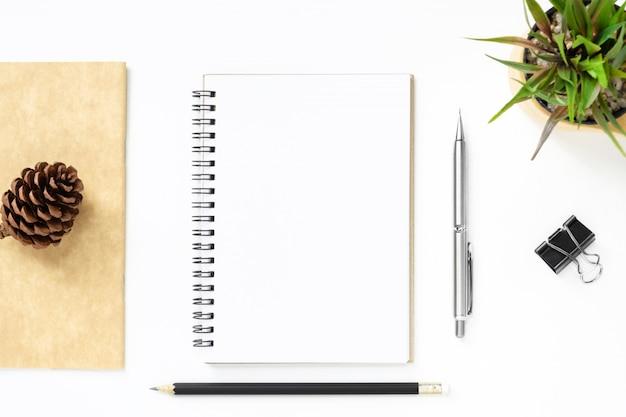 Página do caderno em branco está no topo da mesa de mesa de escritório branco com caneta